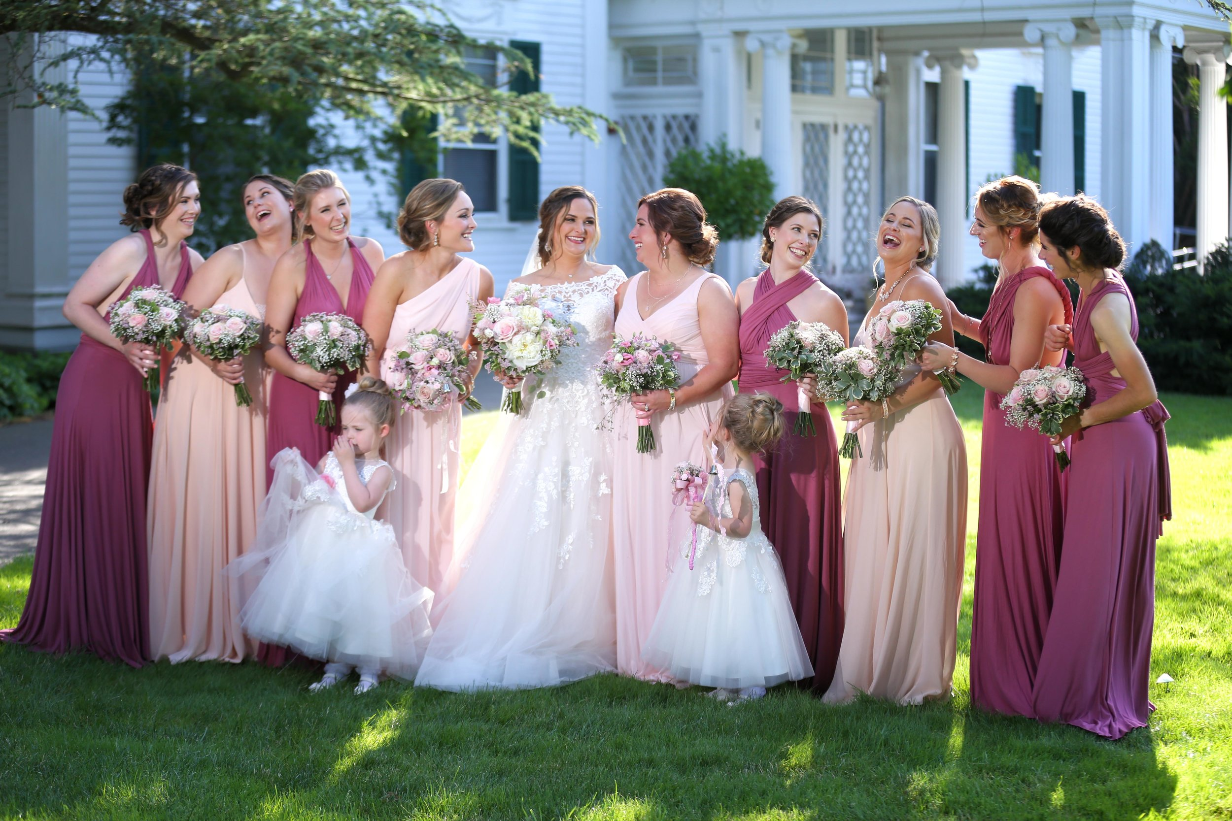 Bride in White empire waist dress & 9 bridesmaids in pink-infinity dresses outside-outdoor-mansion laughing in Morristown-nj
