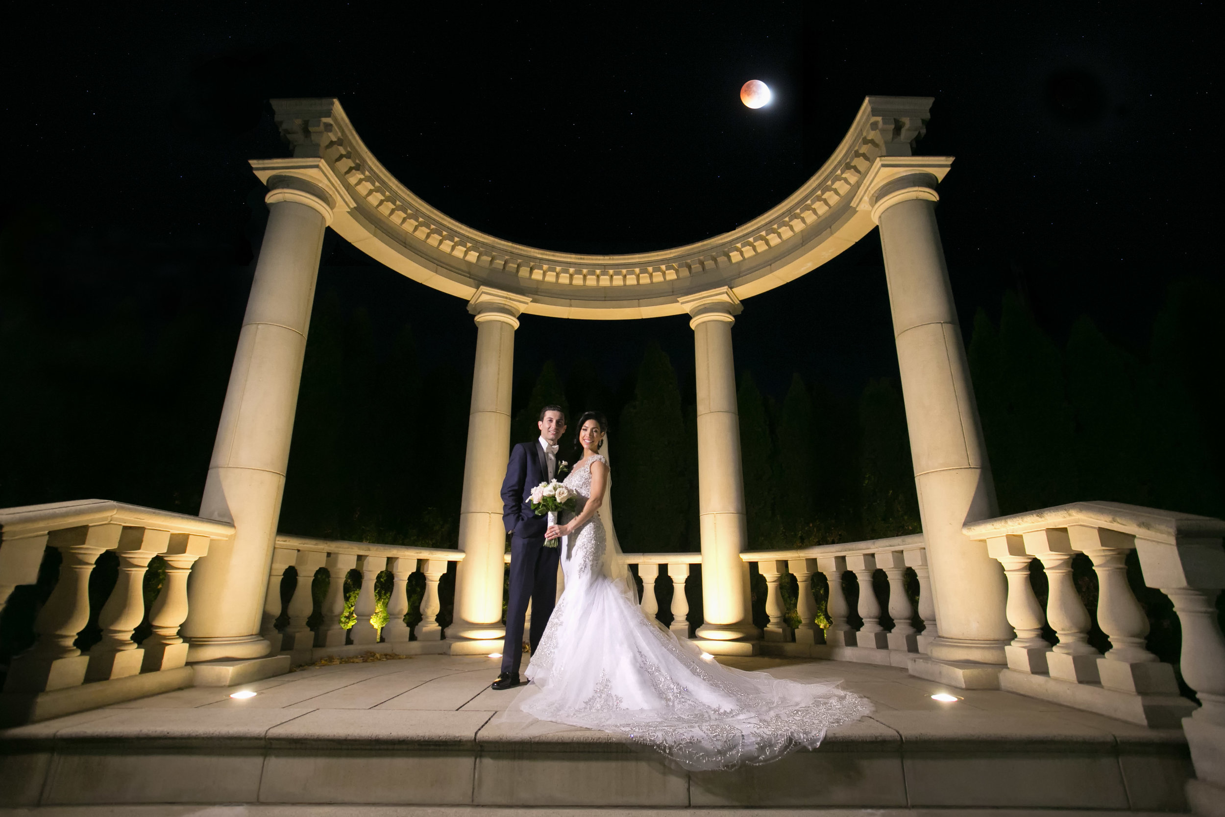 Bride and Groom standing under a blood moon under marble columns.