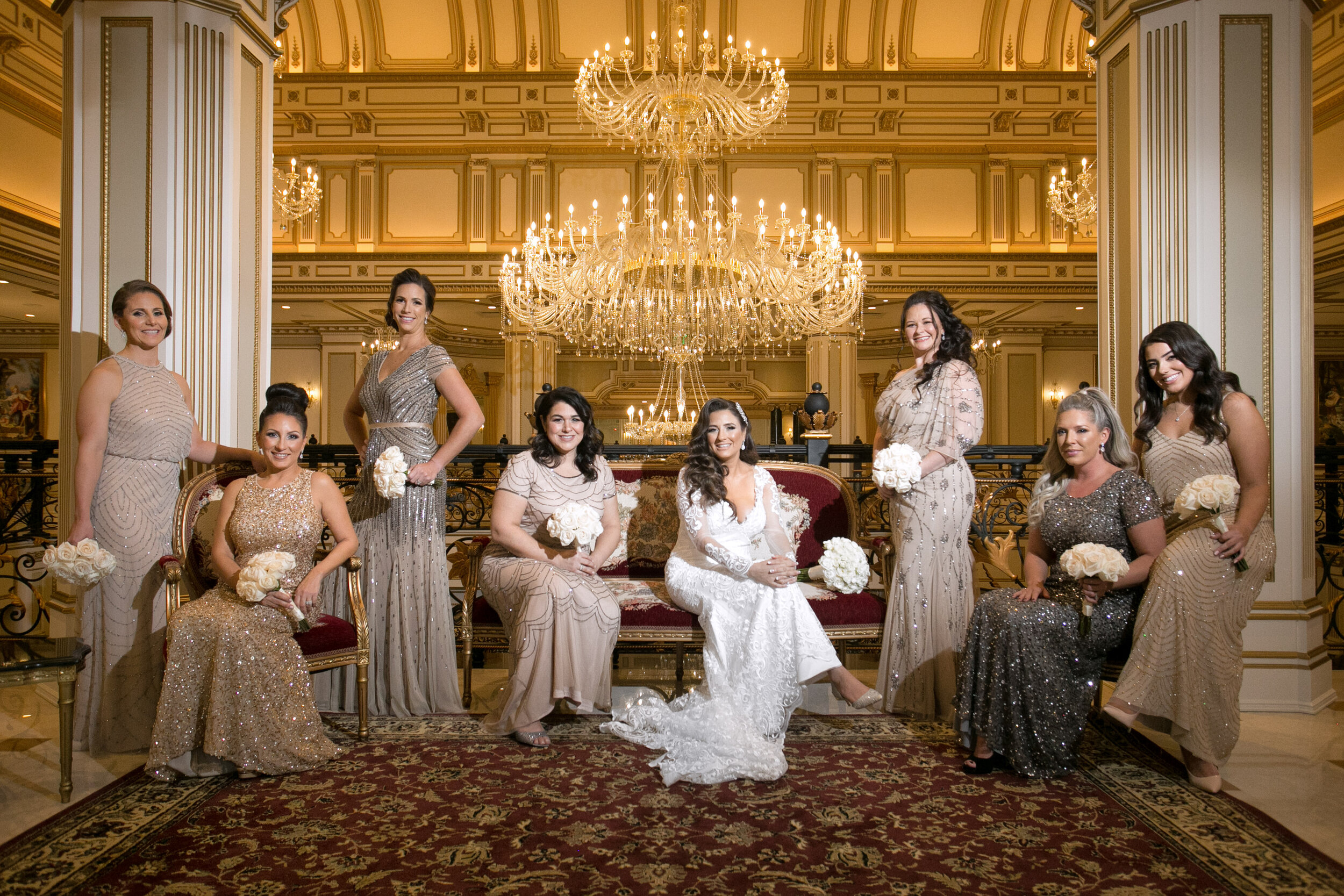 Legacy Castle with Bride and 7 brides posing in front of Ornate Chandelier
