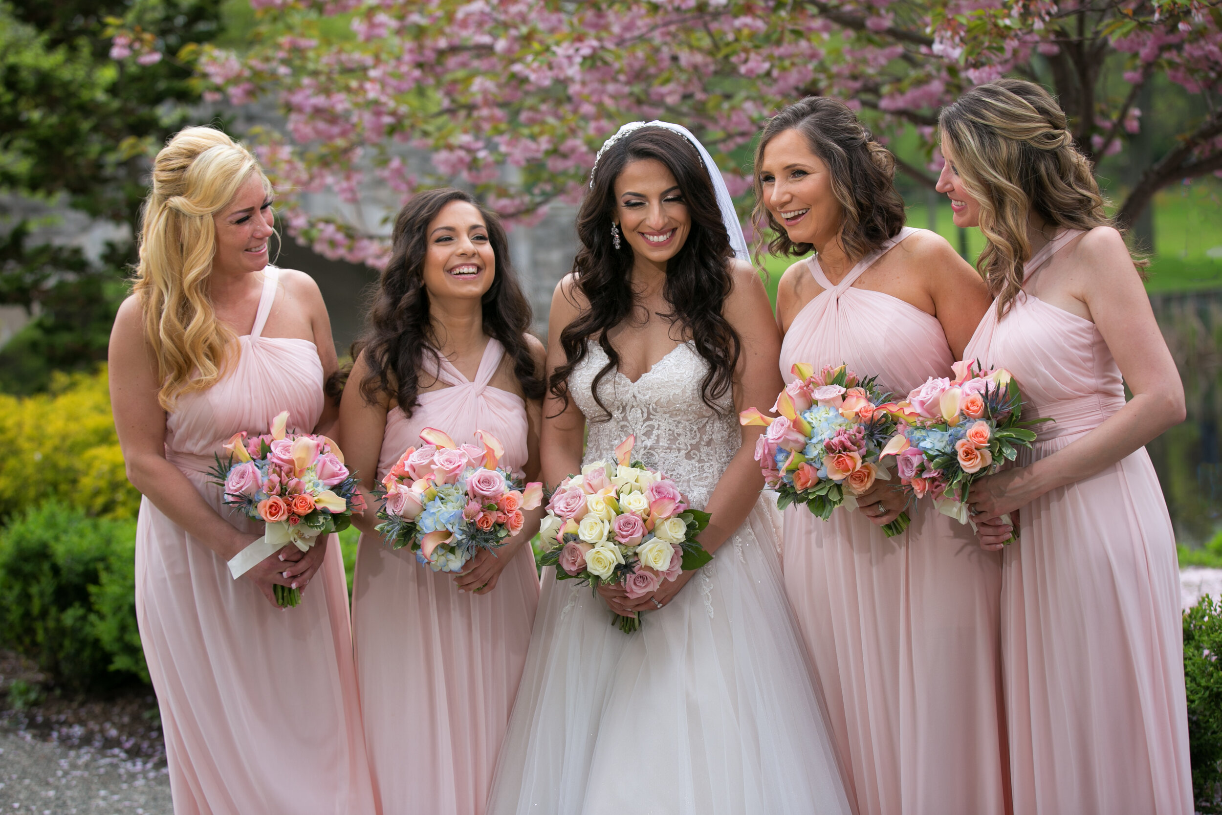 Lightmaster-Studios-Spring-Bride-in-white-standing-with-bridesmaids-in-pink-gown-in-front-of-flowering-cherry-tree-verona-park-nj-.jpg