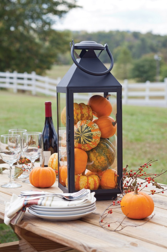 An easy addition to any table, a storm lantern with pumpkins - www.celebratemag.com