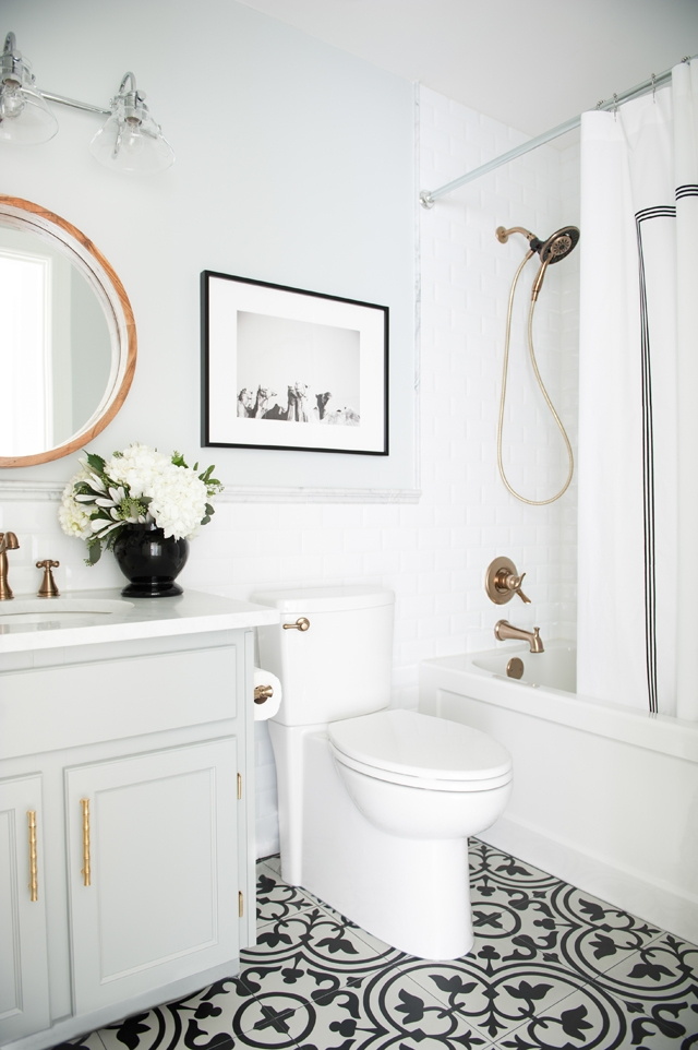 Another beautiful monochrome bathroom with patterned tiles and brass accessories -  www.marcusdesigninc.com
