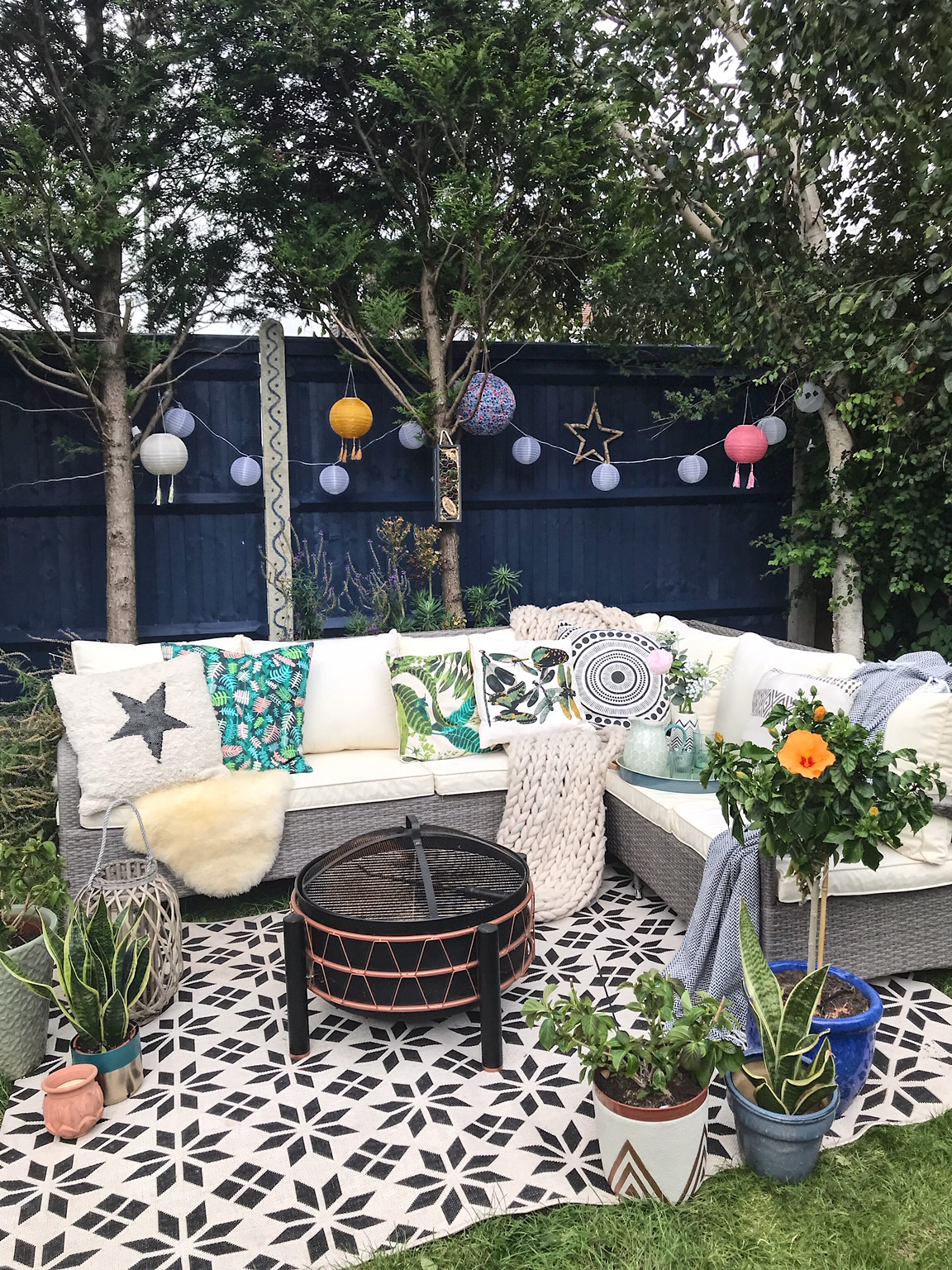 What an amazing back drop to our garden. Fence painted in  Cuprinol  Iris.  Lanterns  from lights4fun.co.uk.  Rattan furniture  from Argos Home.  Rug  from La Redoute.  Fire Pit  from Von Haus.  Knitted throw  from Cox & Cox