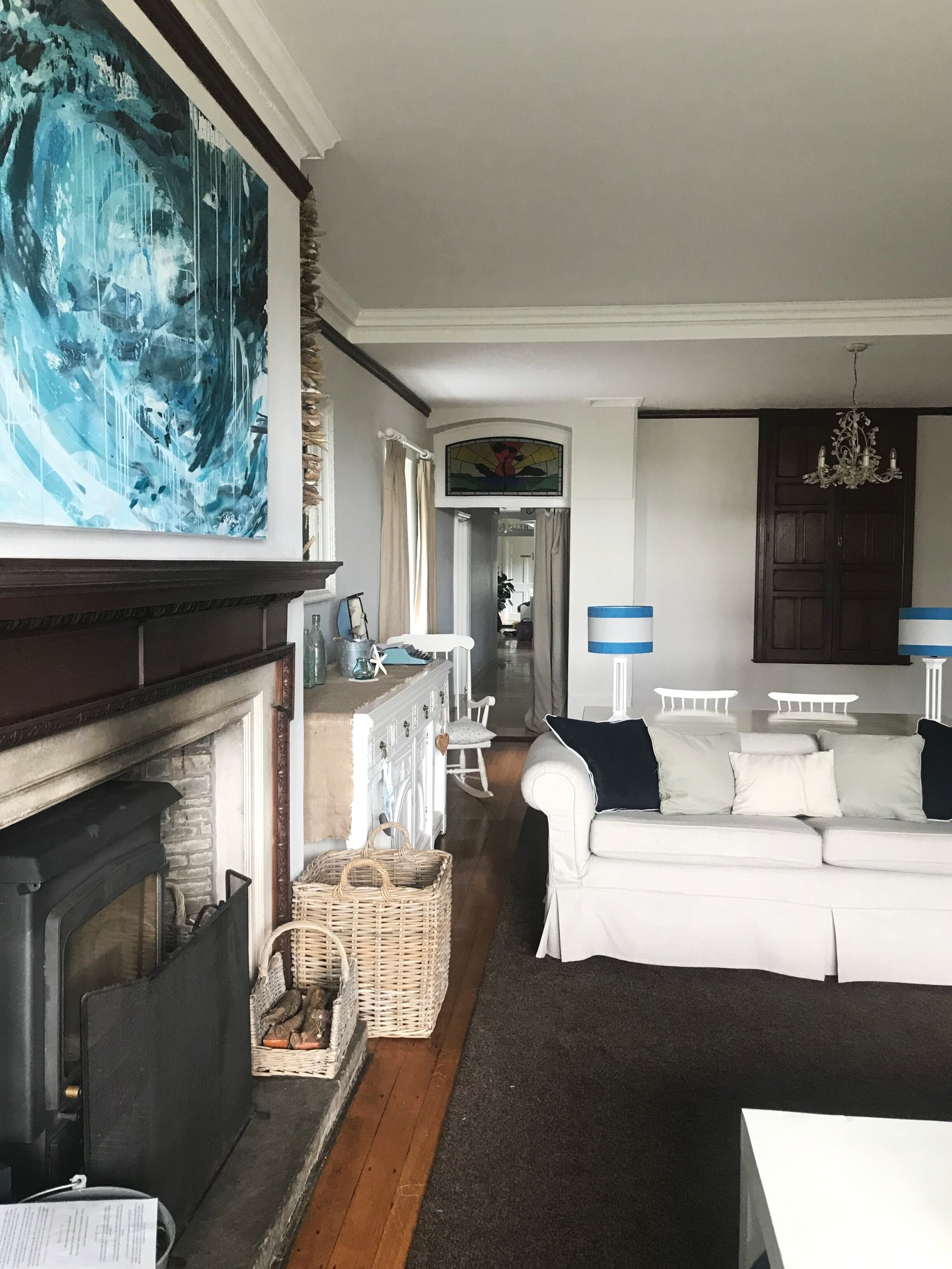 Old and new. A imposing fireplace with pops of blue from abstract art and soft furnishings