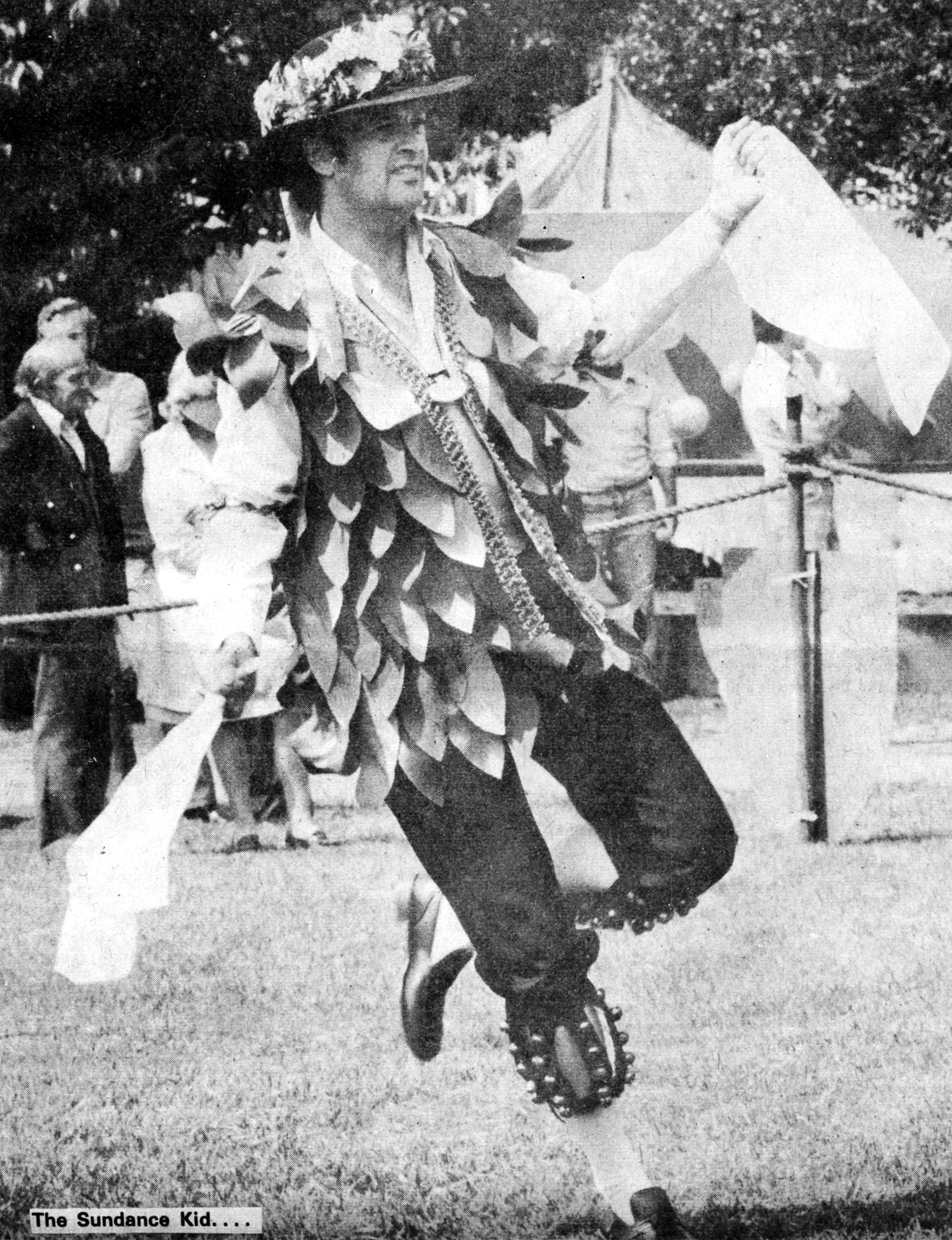 """n 1977, I was """"Foreman of the Morris"""" with English Miscellany - here dancing a jig (Princess Royal - Fieldtown) in Radlett (Herts.) on 9th July. Photo scanned from a copy of the local paper.Note the 19 inch hankies. Specially made as I found a reference in The Morris Book to using hankies that size- much larger than you buy in the shops. Looks much better than the normal ones. The jacket was made for three musicians - myself, Tony Barret, and Graham Lyndon Jones, by Tony B's wife. Sadly Tony B and Graham are no longer with us. I wore it recently as a costume when singing in a concert as Papageno, from The Magic Flute!"""