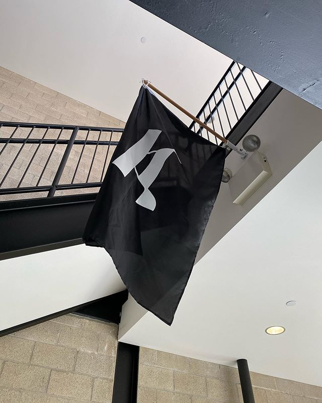 Installation view of a flag by Professor Kaleb Dean. The flag features a specimen from his Akimbo.black typeface.