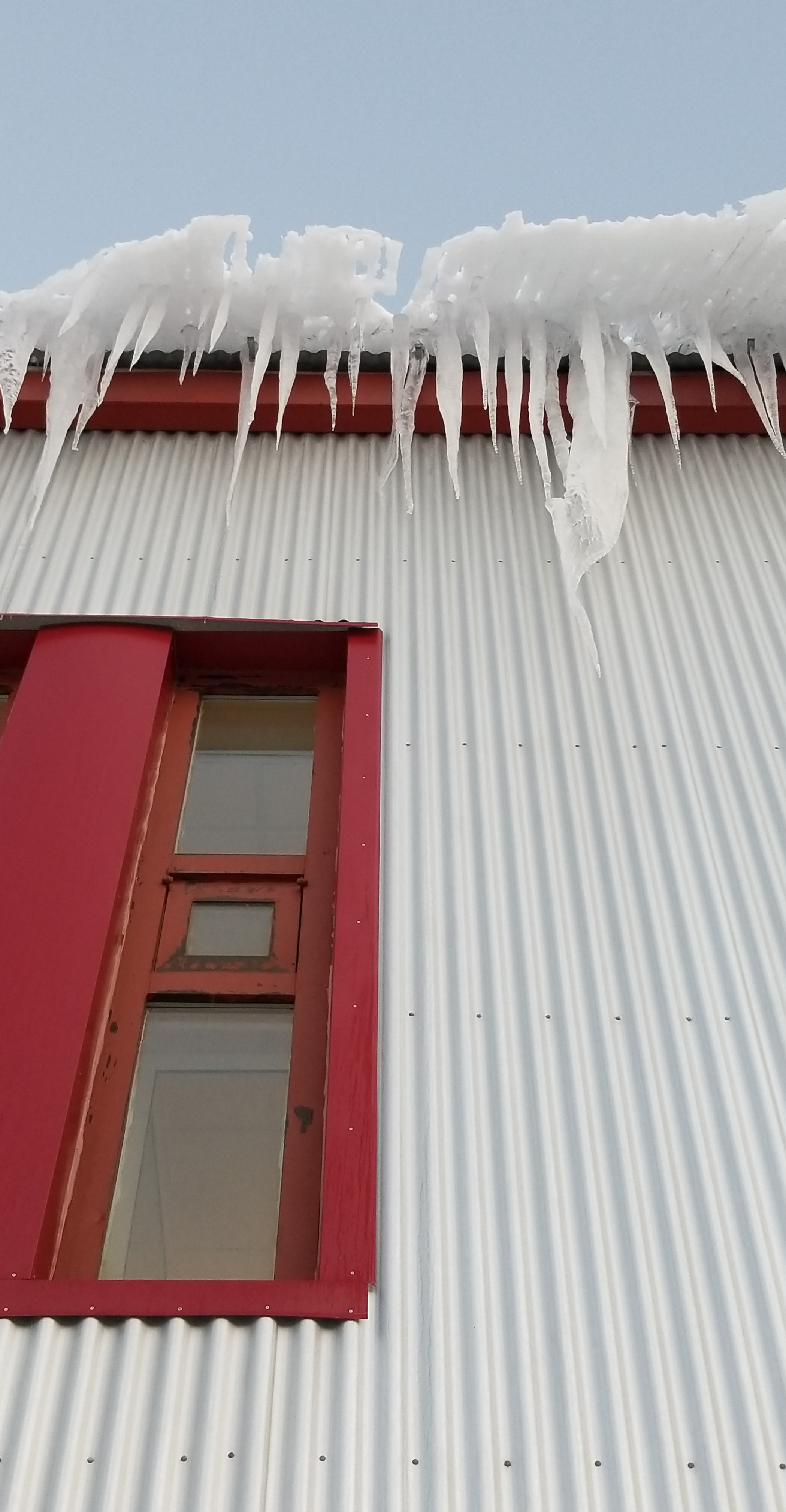 Icicles falling from a rooftop in Bolungarvík, Westfjords