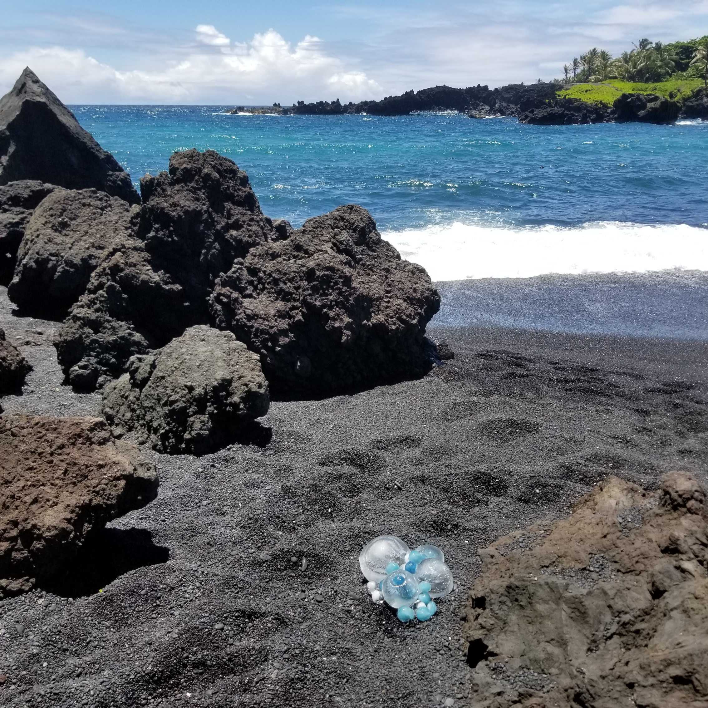 Blue butterfly pea infused ice installation melting fast on the black sand beach at Waianapanapa in Maui, June 2018.
