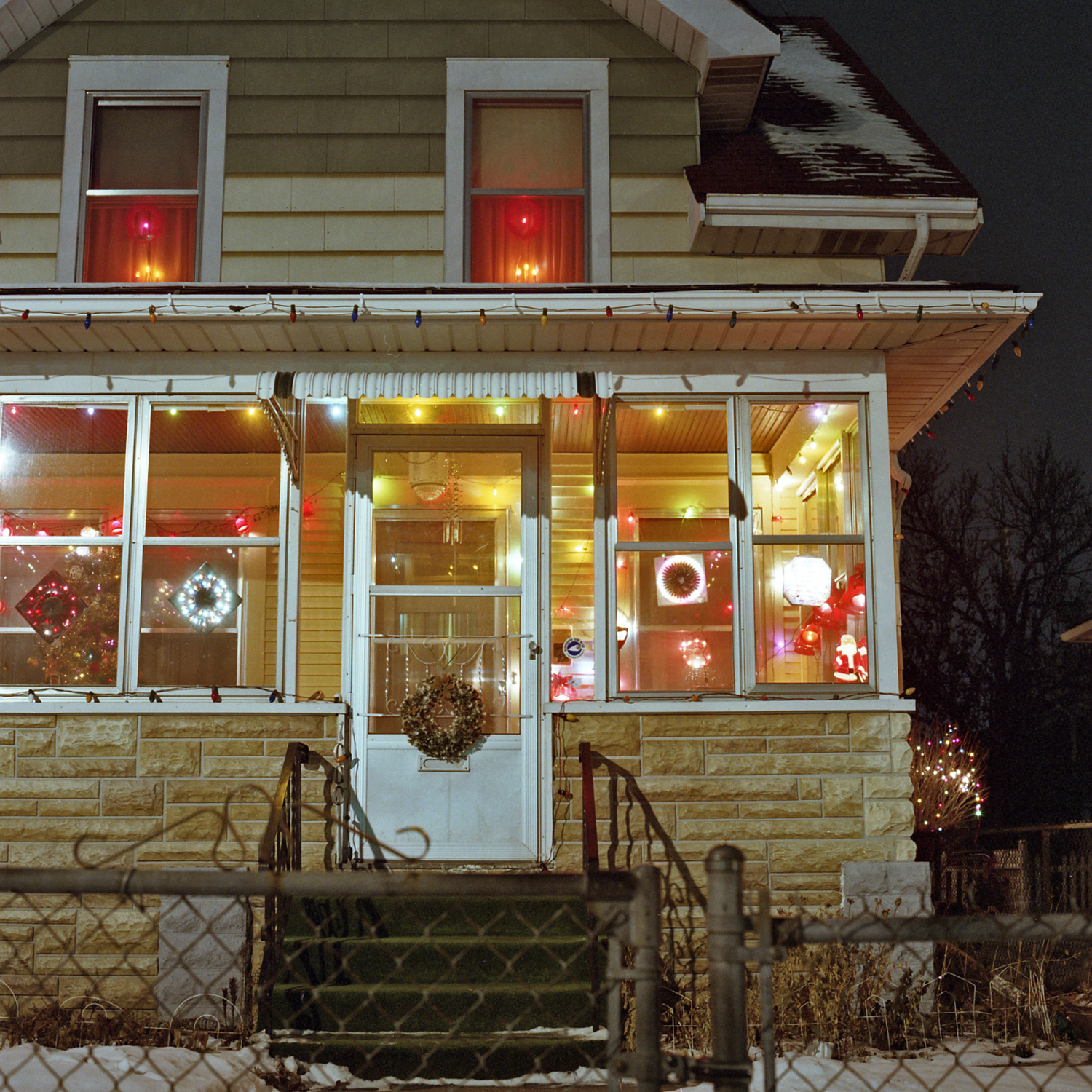 Aurora Avenue, Saint Paul, Minnesota. January 1990. Series of modest homes in the Frogtown neighborhood illuminated by Christmas lights still in their display boxes; an efficient method for seasonal decorating!