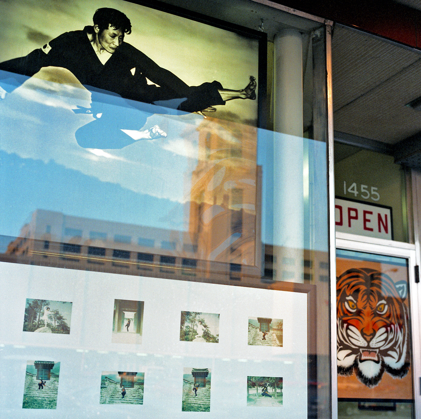 Chun Moo Quan, University Avenue, Saint Paul, Minnesota, March 1989. Martial arts practitioner executes a high-kick over the reflection of the Wards store tower across the street (torn down and replaced by shopping mall including a Herbergers store, recently closed, T.J. Maxx and Cub Foods).