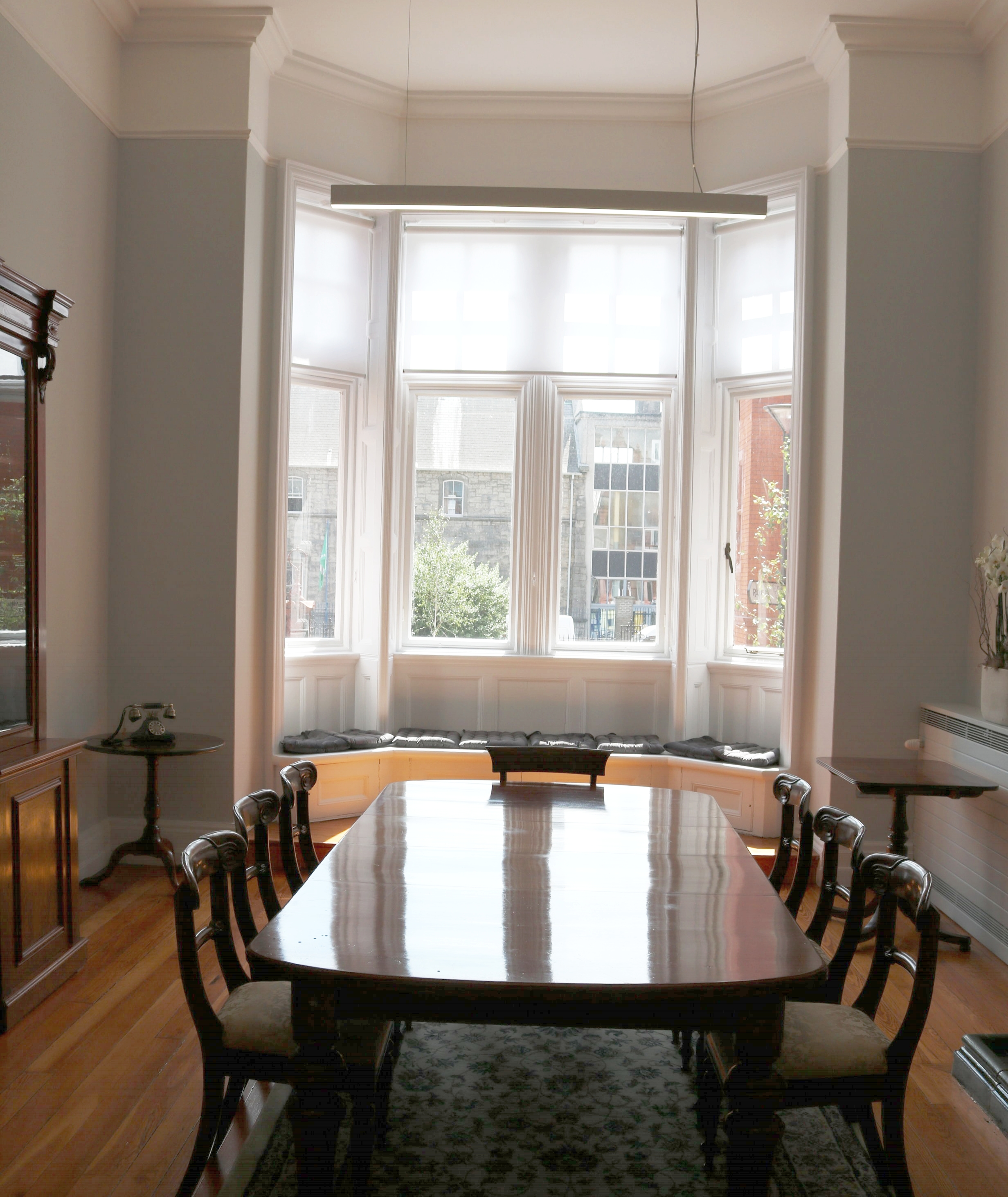 Drawing Room - The drawing room boasts original wooden floors and fireplace as well as antique furniture providing a comfortable space for small meetings. A bay window provides a stunning view of our carefully manicured gardens and round courtyard, the focus is which is an elegant fountain.