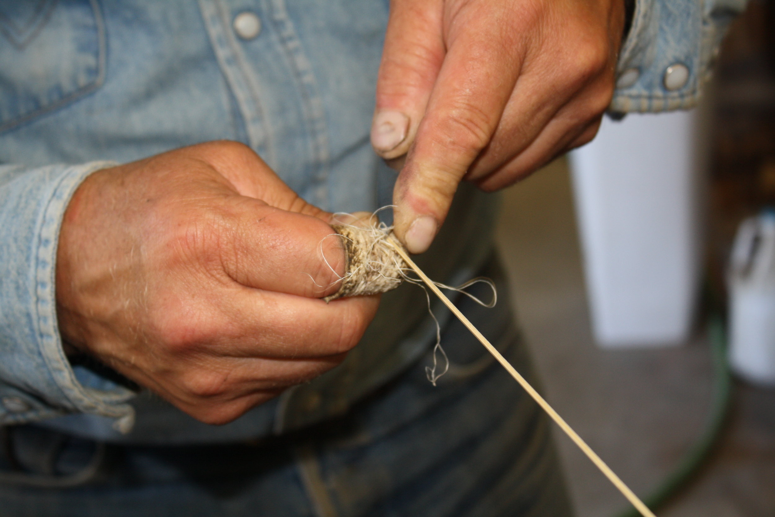 Minor bevels a piece of rawhide string, removing any rough edges to ensure evenness throughout.
