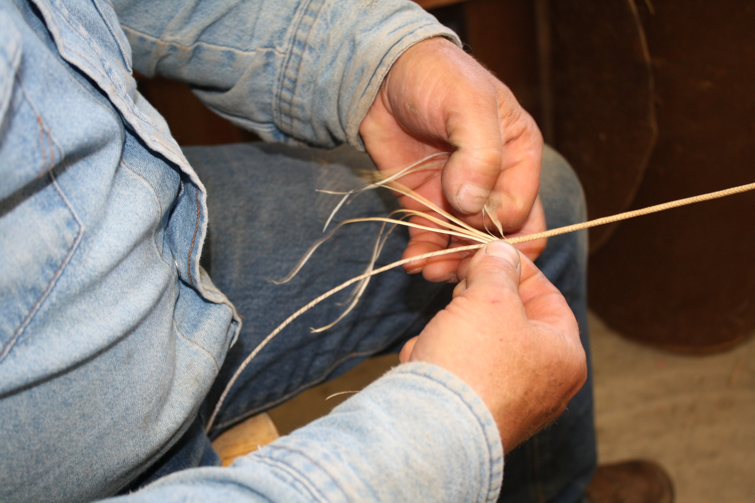 Minor says it's important to keep the tension the same on each string as he braids a horsehide bracelet.