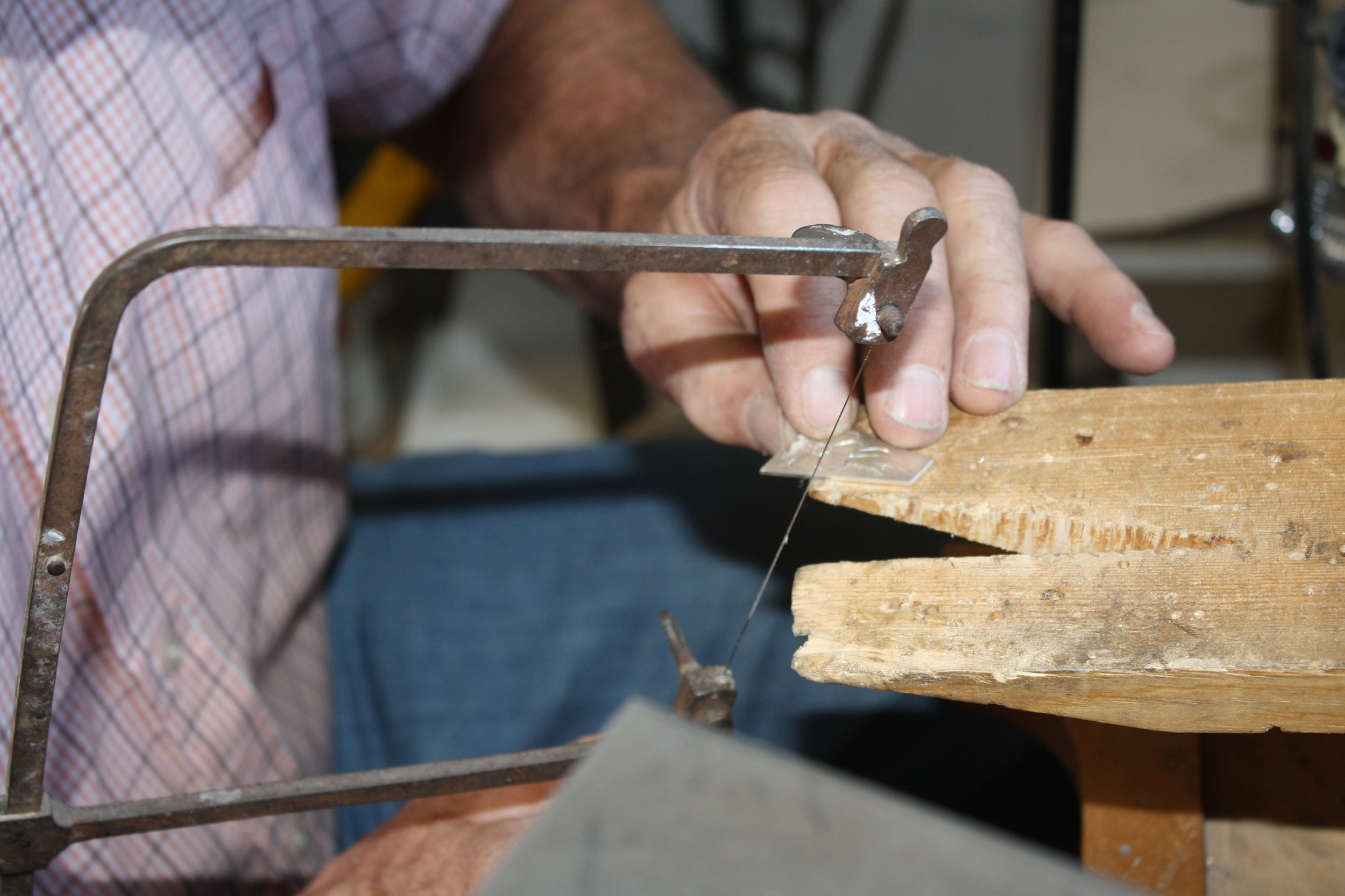 Jock Brown cuts a floral design from a sheet of silver using a jeweler's saw.