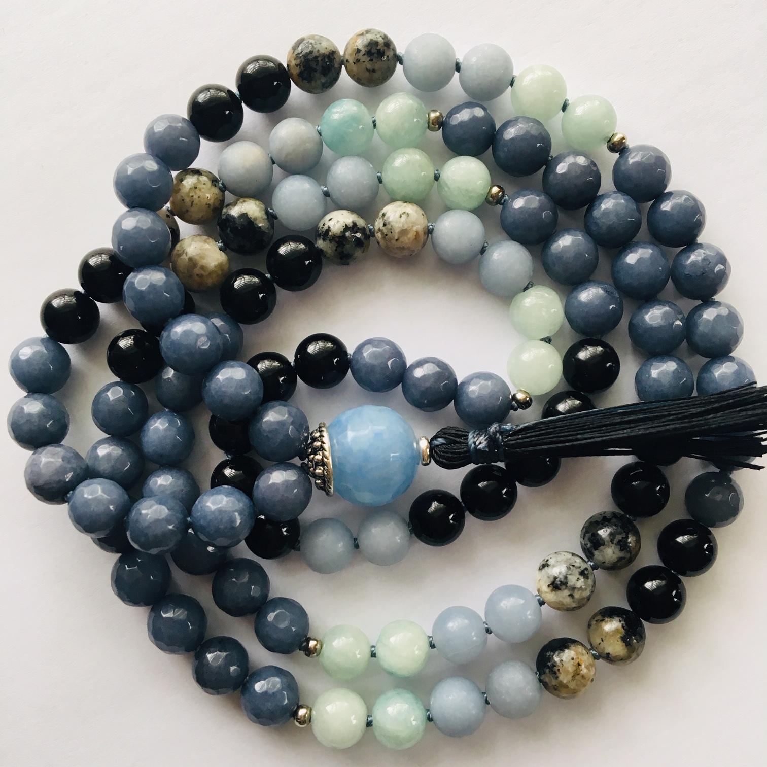 Honor Your Depth Mala  (8mm)  Sapphire Jade (dark blue) is a stone of wisdom and provides a break through in understanding, Aquamarine (light blue green) is a calming and soothing stone that inspires truth and trust, Angelite (blue) helps relieve tension and stress and helps you speak your truth, carries the vibration of grace, Jasper (black-grey) helps manifest strength, courage and wisdom.