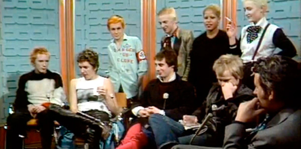 The Pistols on Today with host Bill Grundy, with members of the Bromley Contingent in back, including Siouxsie Sioux, top right