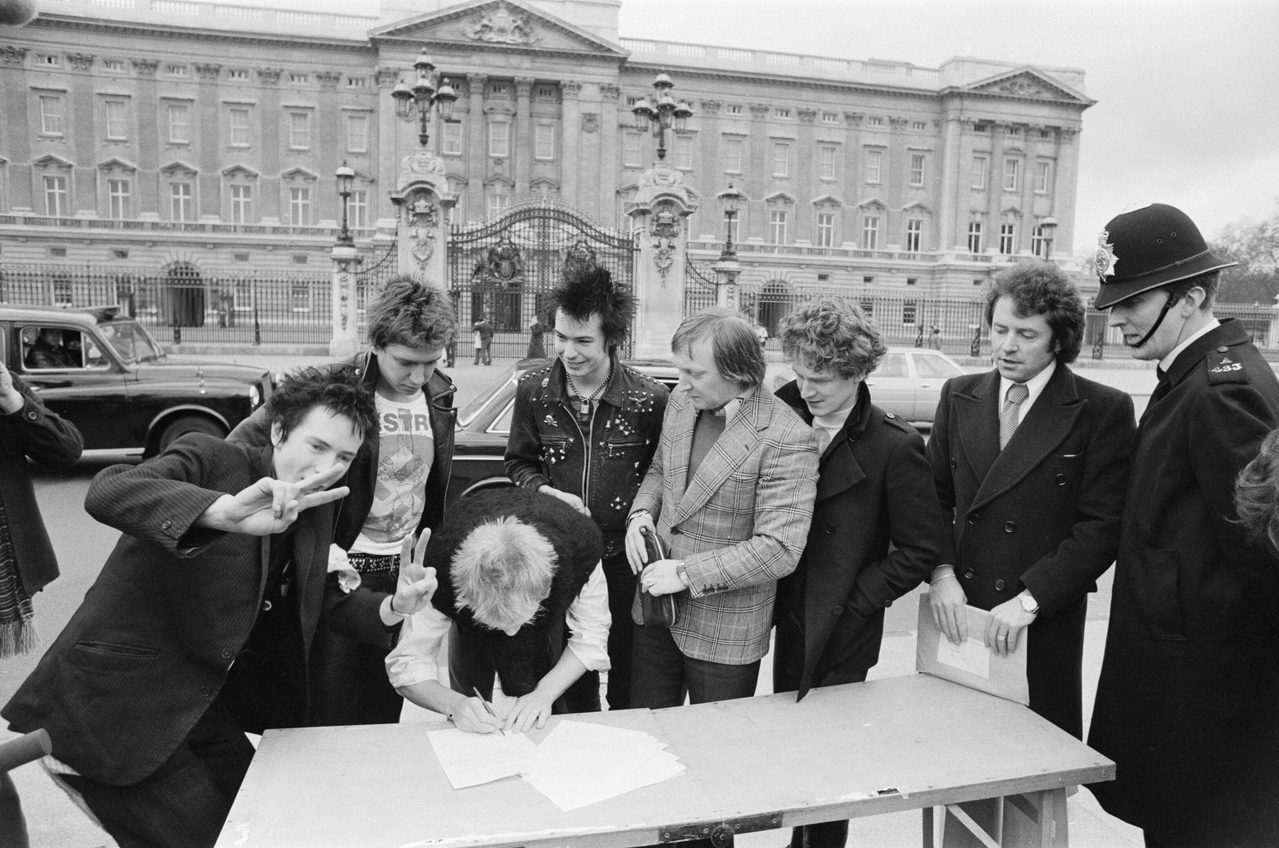 The Sex Pistols contract signing to A&M in front of Buckingham Palace. L to R: Johnny Rotten, Steve Jones, Paul Cook (signing), and Sid Vicious. Malcolm McLaren is third from right.