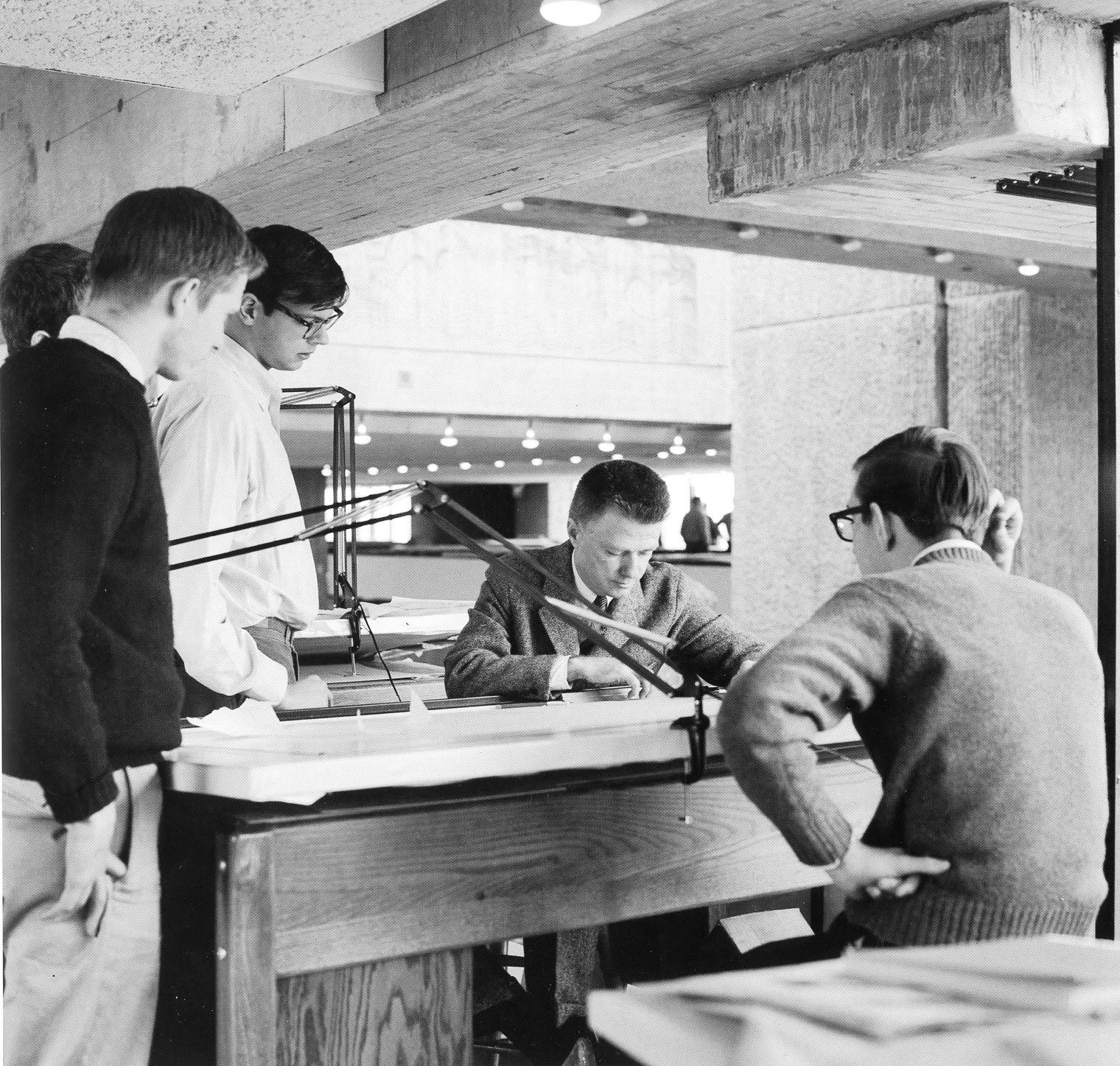 "Paul Rudolph with architecture students in the Yale Art & Architecture Building, giving a ""desk crit"" in 1963. Photo: copyright Ezra Stoller"