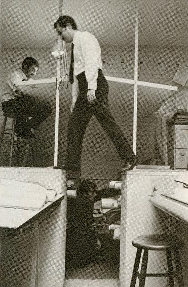 """Of all the photos we've seen of the insides of Paul Rudolph's various offices, this is one that intrigues us most. In this version of the drafting room, the lower level was used for """"tube storage"""" of rolled-up architectural drawings, and drafting stations were positioned on platforms above. Errol Barron says that's a photo of a staff member of Rudolph's office, Max Lieberman, stepping across the gap—and describes that getting around the office as having its adventurous side.. Image © The Estate of Paul Rudolph, The Paul Rudolph Heritage Foundation."""