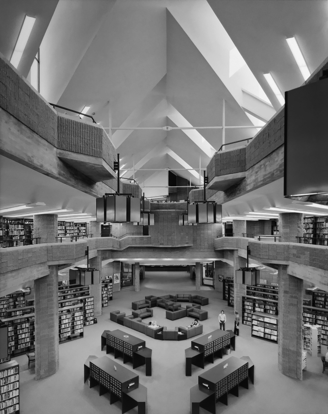 The library's atrium-interior, as photographed in 1972. This view allows one to see all three levels, as well as the ceiling openings to the clerestory windows (in the angled roof) which bring natural light into the space. Joseph W. Molitor architectural photographs. Located in Columbia University, Avery Architectural & Fine Arts Library, Department of Drawings & Archives
