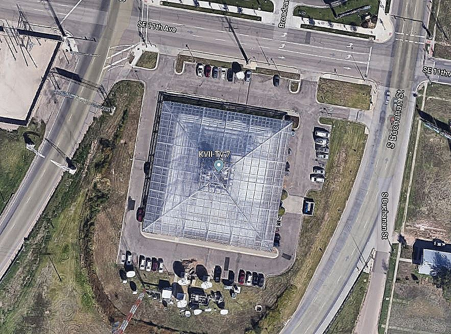 A closer-in satellite view, looking down on the TV station's pyramidal roof:    To get a sense of the building's scale, one can compare it with the cars which are parked to the North, East, and South. At the bottom of the picture (at the South, just below the line of parked cars) is an array of the numerous types of antennas used by the station. Image courtesy of Google: Imagery ©2019 Google, Imagery ©2019 Maxar Technologies.