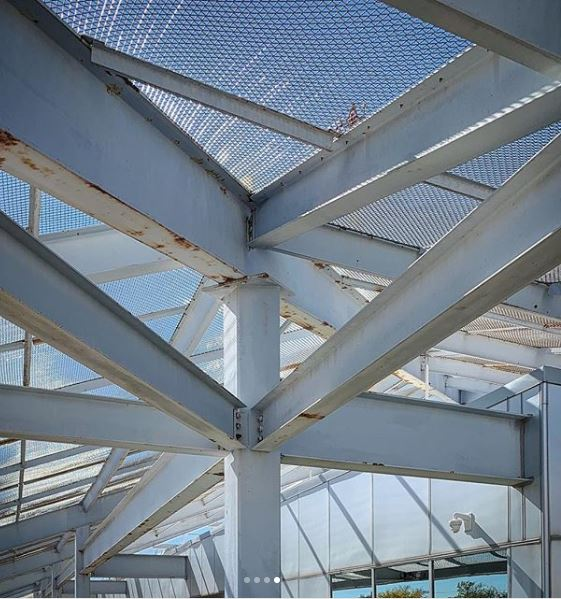 A view from below the pyramid's roof. The steel structures appears to support an open mesh sheathing, and the enclosed body of the building seems to be composed of a metal & glass curtain wall system. Photo © Ben Koush, used with permission.