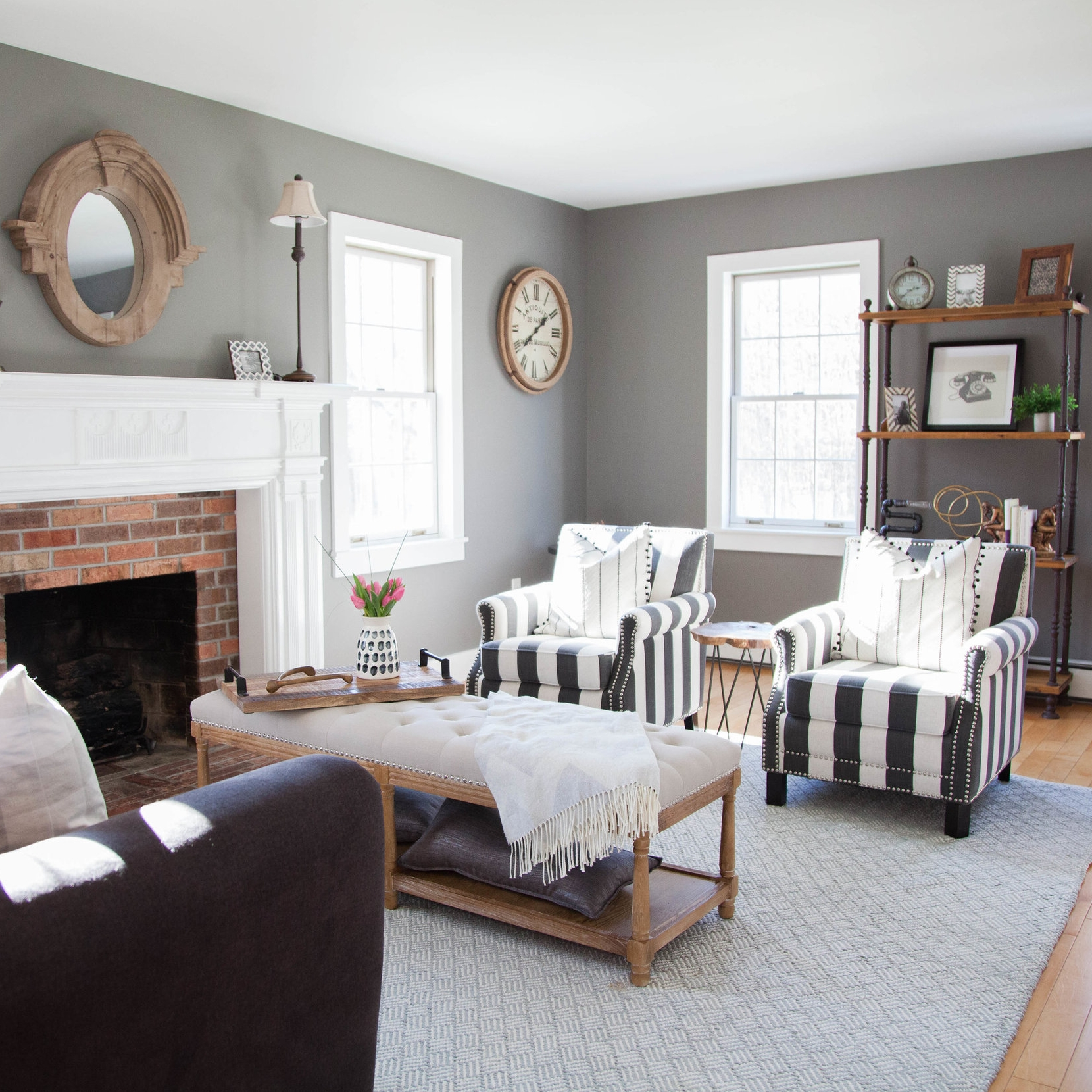 Living room sitting area with chairs and couch, plus exposed brick fireplace