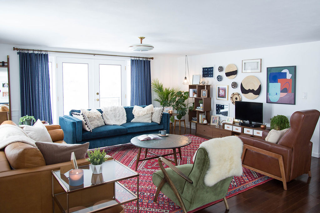 Living room with leather couch, blue couch, red rug, gallery wall
