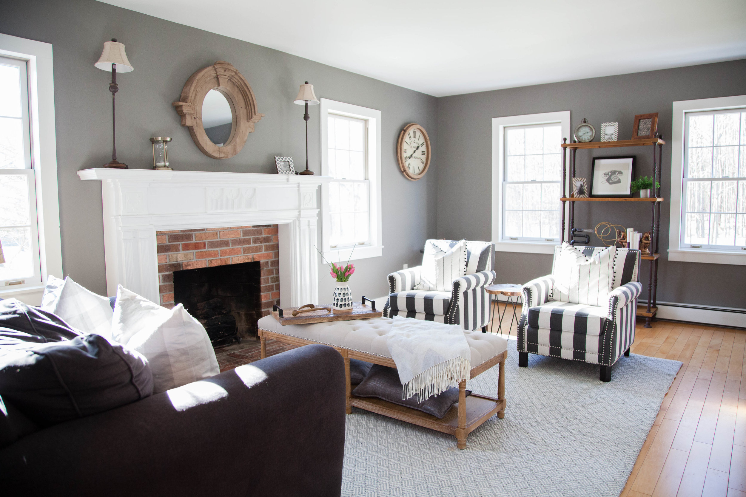 Living room with couch and chairs, grey walls, and fireplace in Hamilton, NY