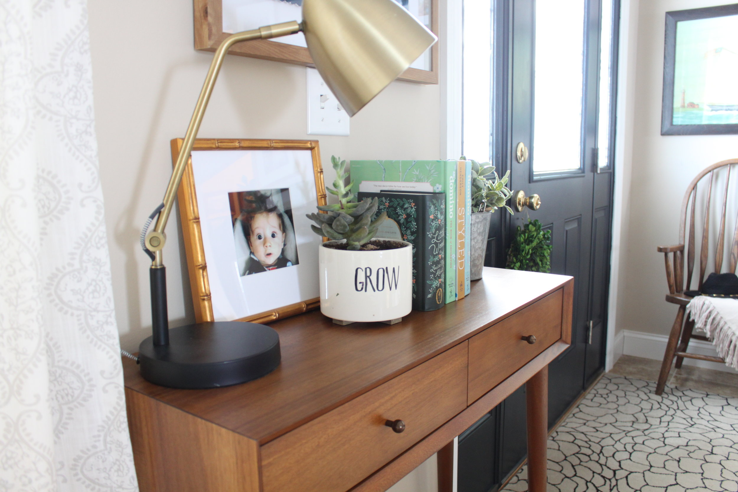 Wood entry table with gold lamp, framed photo, faux plant, and black front door with natural light
