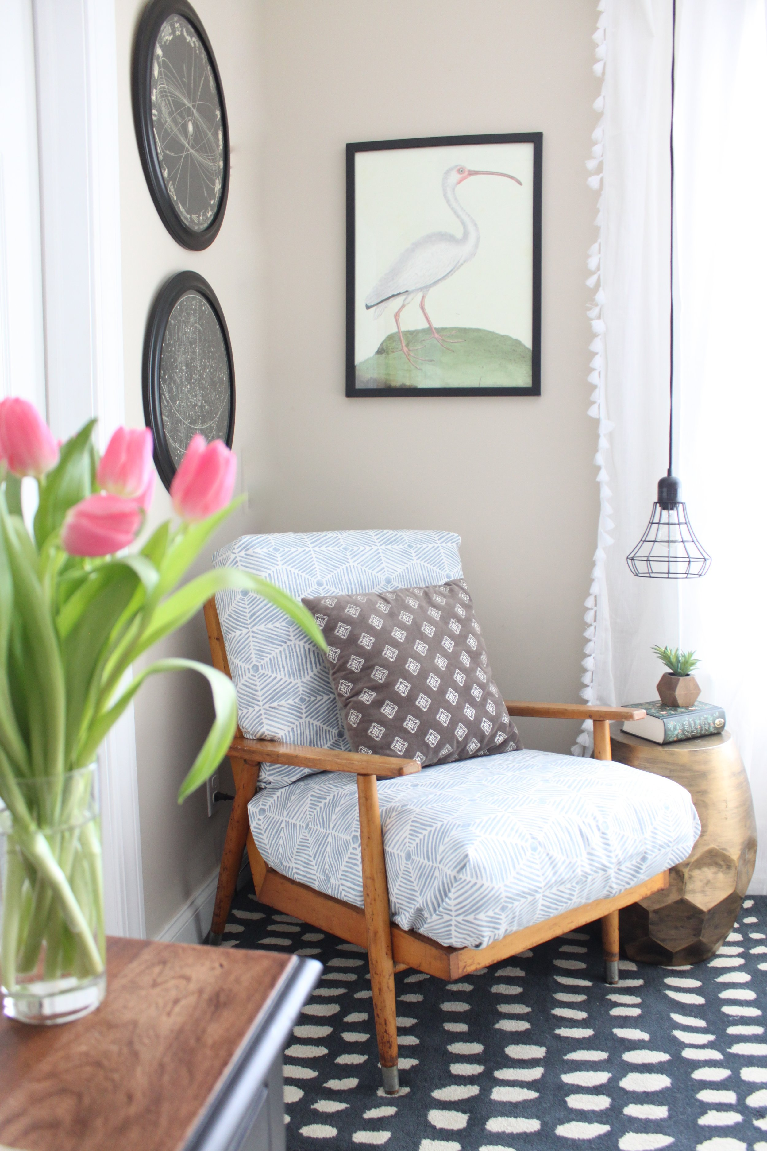 Office corner with reading chair, hanging lamp, and fresh flowers
