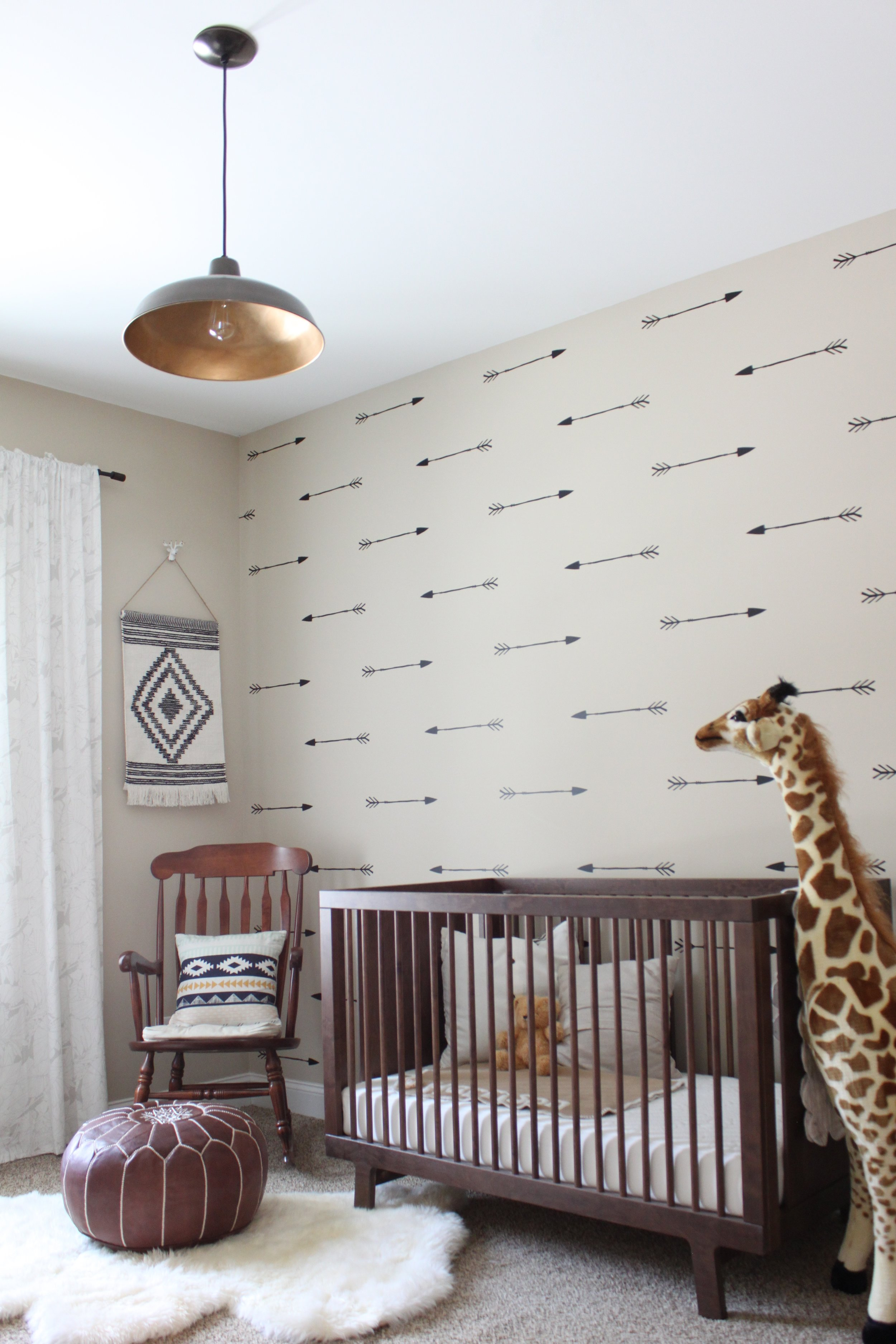 Nursery with wood crib, accent wall, hanging light fixture