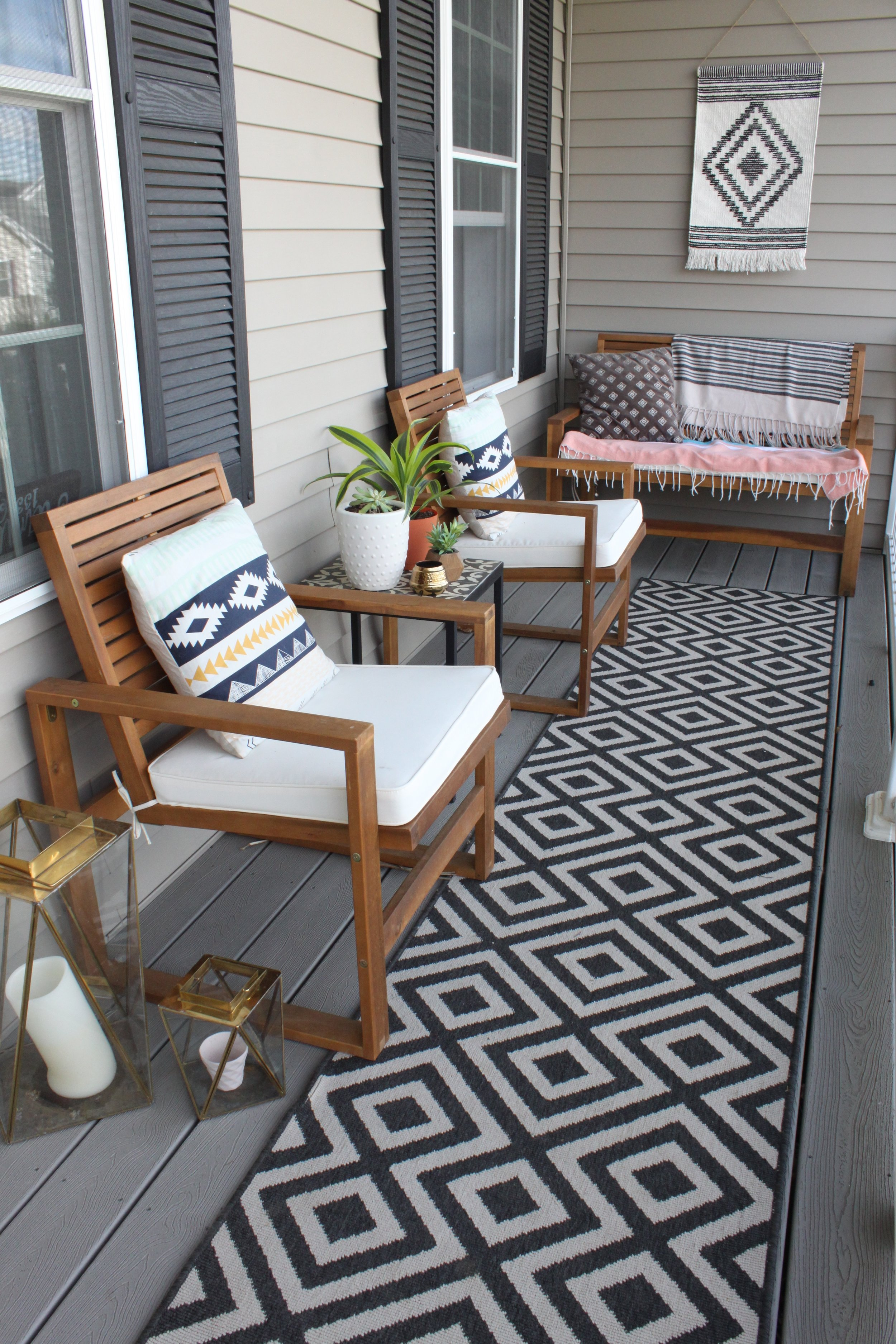 Porch with chairs, bench, decorative rug, hanging artwork