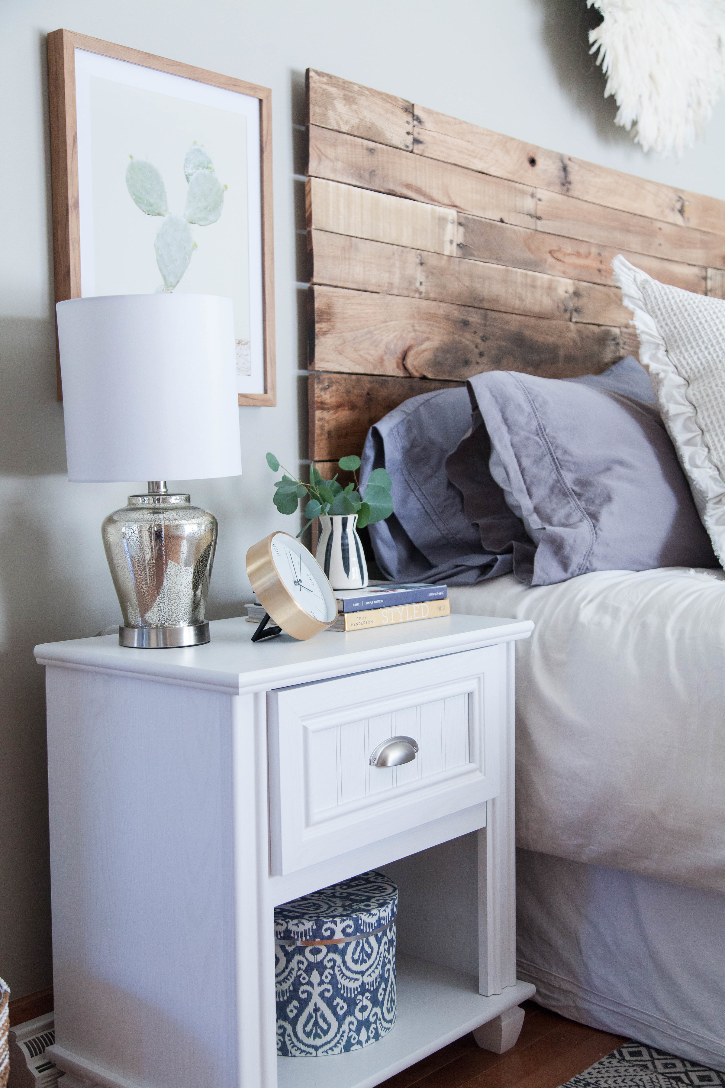 Guest house bedroom nightstand with mixed metals and handmade wood headboard in Hamilton, NY