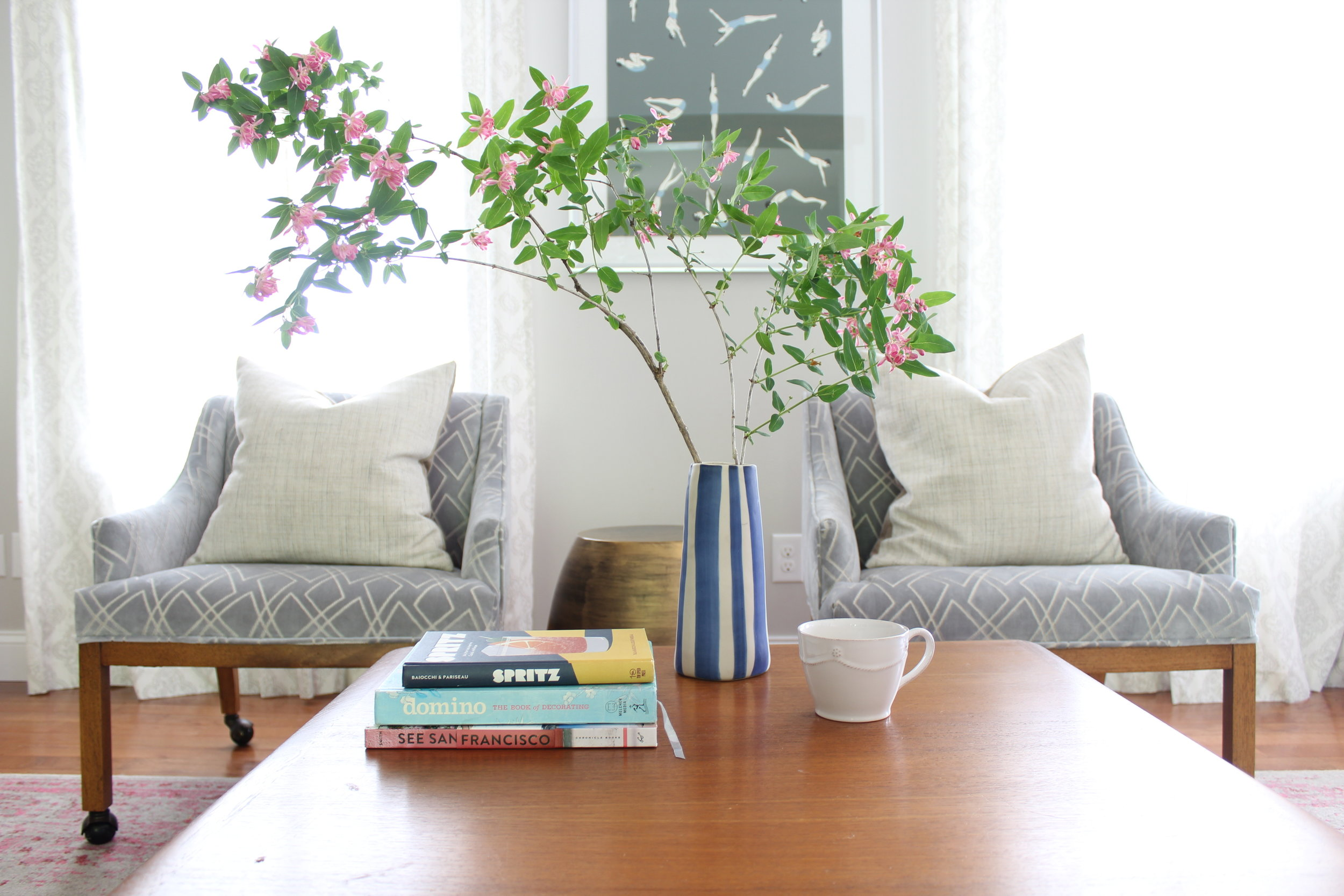 Stem arrangement in front of matching wood chairs with pillows