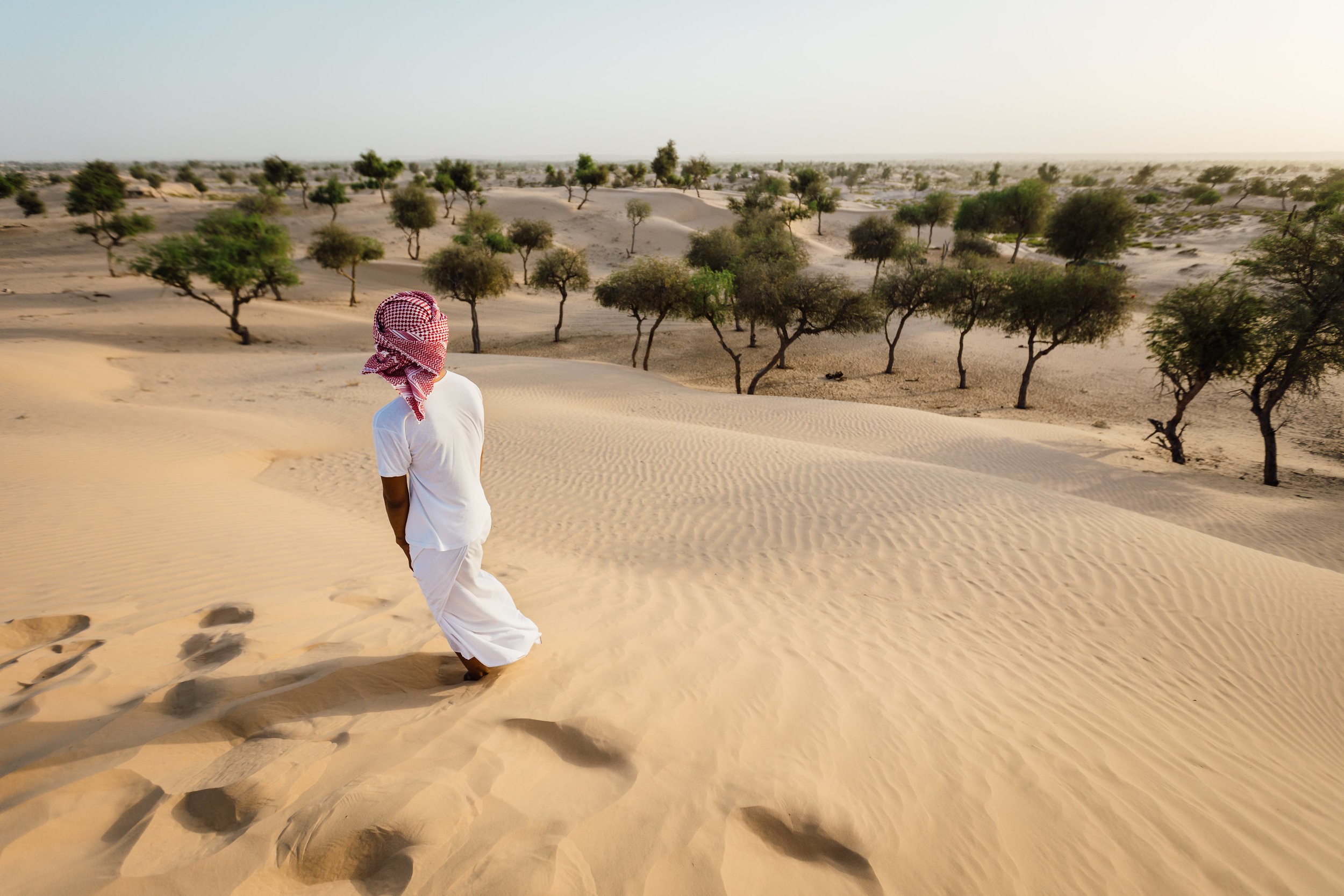 A young Omani man stares off into the distance of the desert of Sharqia.