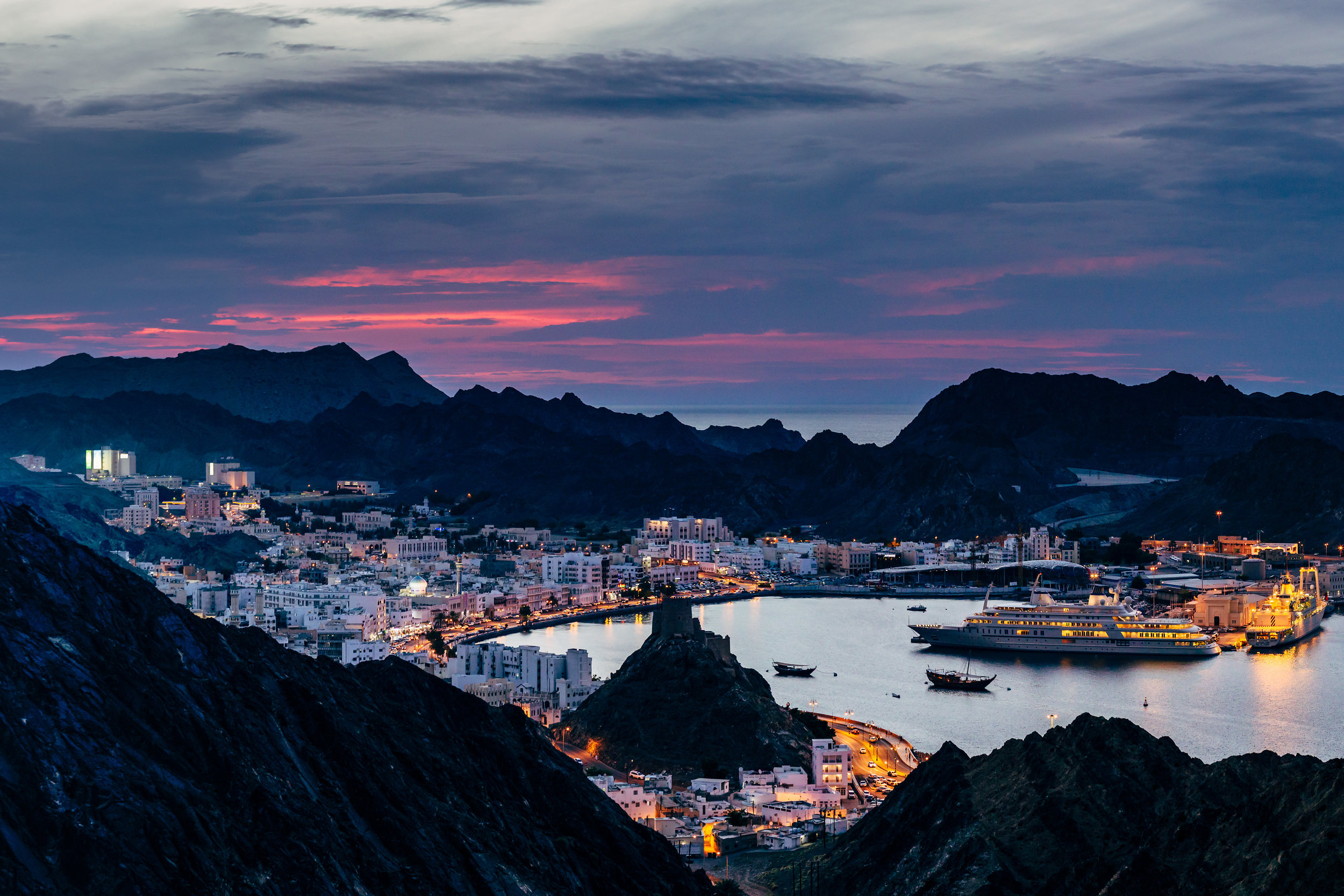 The sun sets behind the old city of Muttrah, one of the oldest ports in the Middle East.
