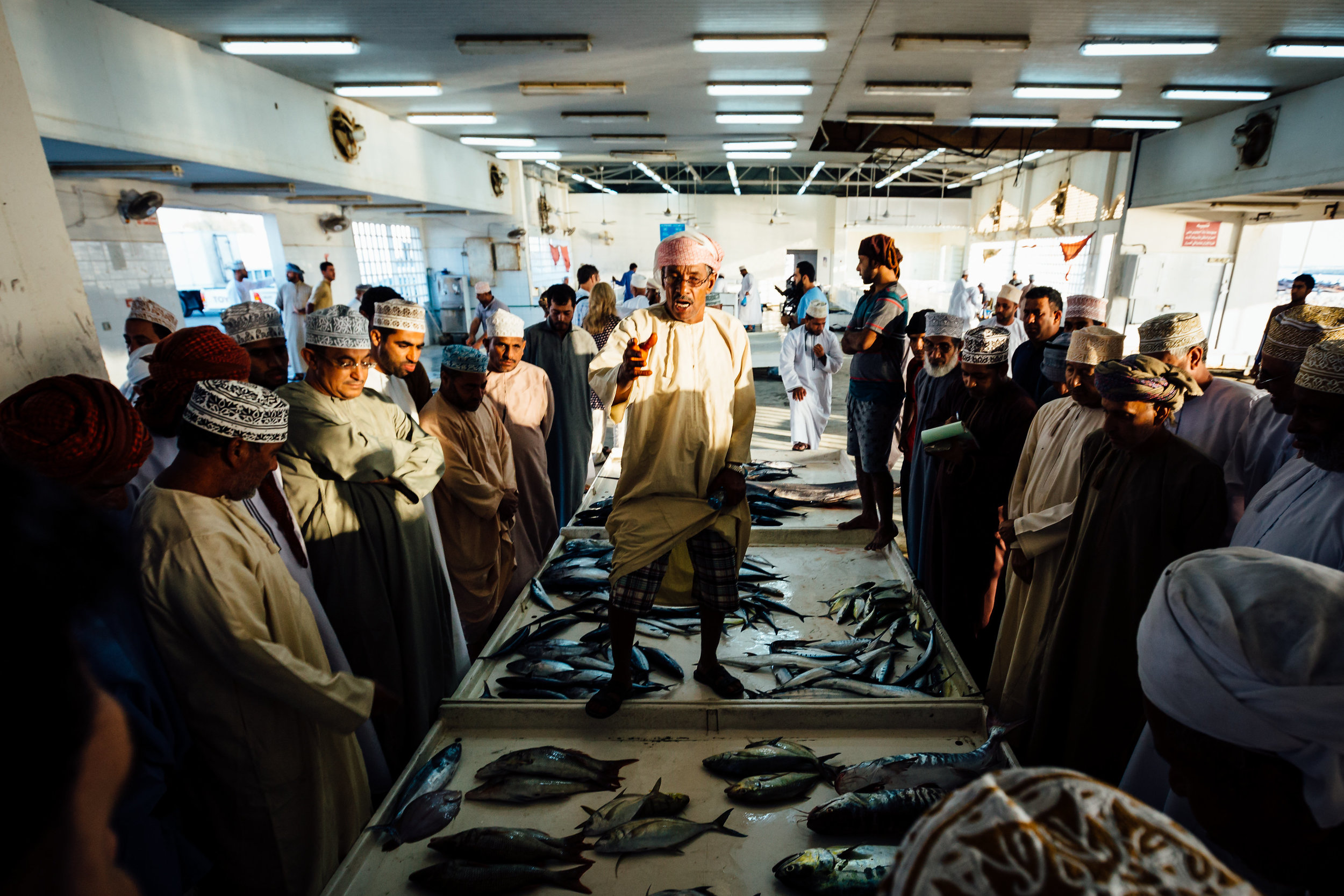 an auctioneer takes bids for freshly caught fish in the coastal village of Quriyat