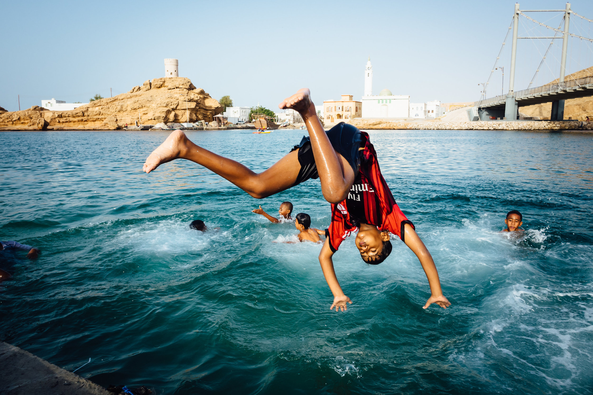 A boy dives off a dock into the cool waters of the ship-building village of Sur.