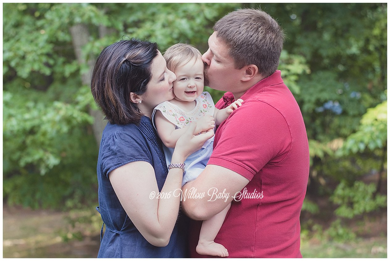 mom and dad holding and kisses their smiling one year old