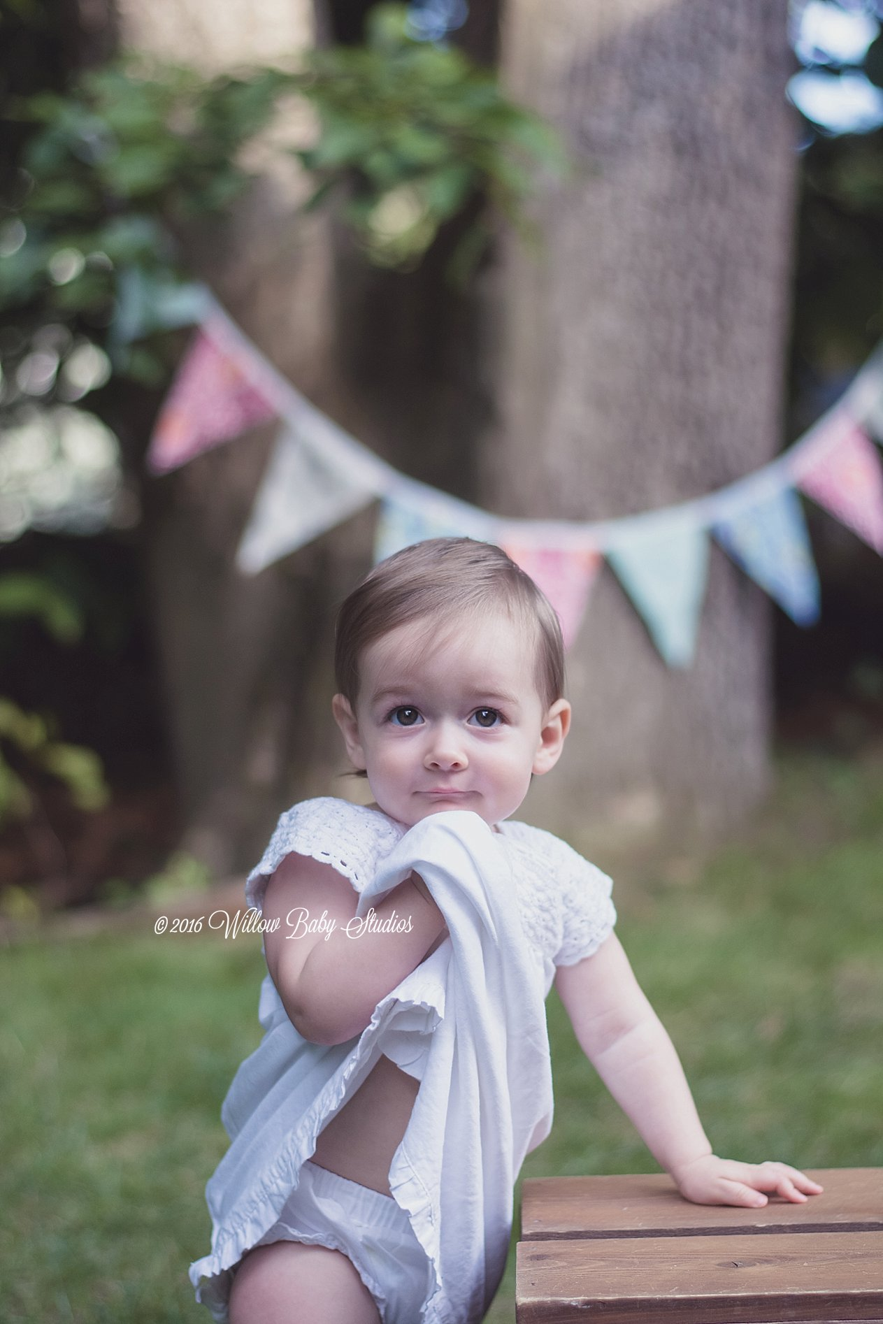 one year old staring at camera holding her dress up to her chin