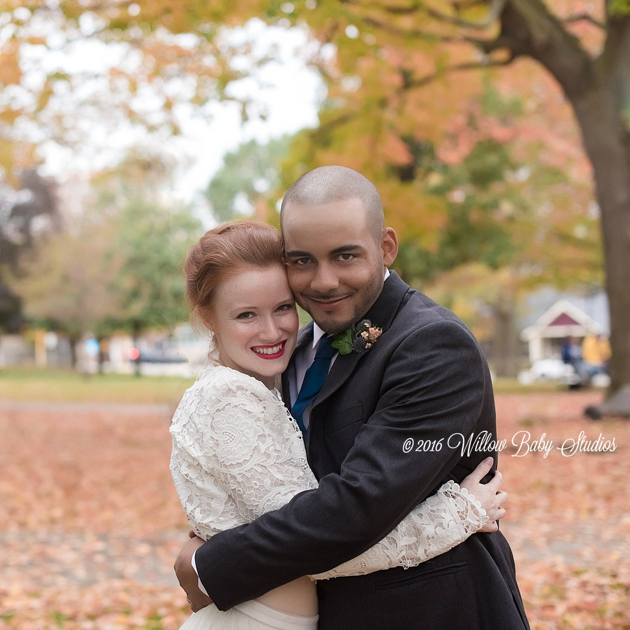 husband and wife embrace on their fall wedding day amidst the leaves