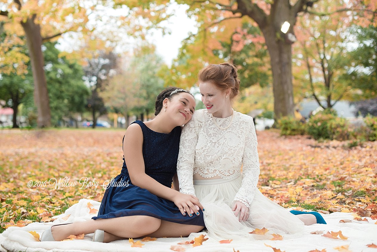 mother and 10 year old daughter sitting in autumn leaves after wedding ceremony