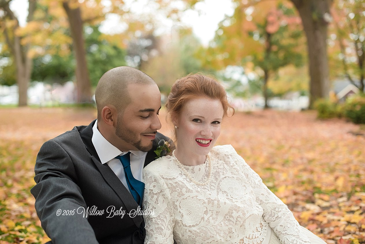 husband and wife sitting in the fall leaves on their wedding day