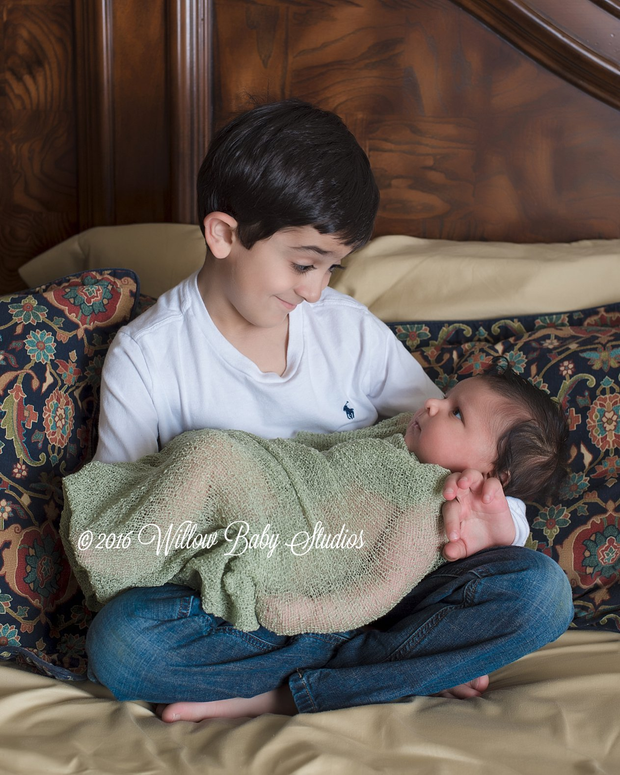 5 year old boy holding his new baby brother
