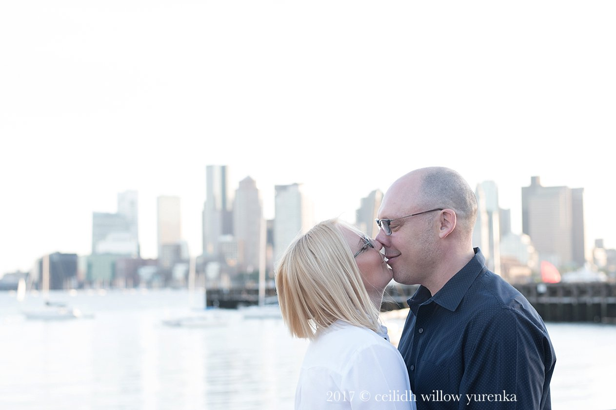 couple kissing near piers park in front of boston skyline