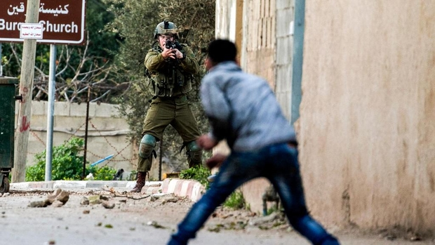 An Israeli soldier points his weapons at a youth during clashes in Burqin in February 2018 (AFP)