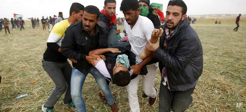 Palestinian protesters evacuate a wounded youth during clashes with Israeli troops along the Gaza Strip border