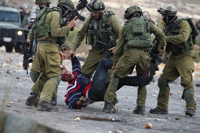 Israeli soldiers detain a Palestinian stone thrower near Beit El