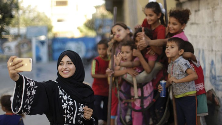Fatma Abu Musabbeh , 21, uses her cellphone to take a picture for her social media account of children in Deir al-Balah in the central Gaza Strip, Sept. 17, 2017. She and another Gaza woman are among a small number of Instagram stars in Gaza, showing their followers a different side of their homeland than what much of the world may be used to seeing or hearing. (MAHMUD HAMS/AFP/GETY IMAGES)